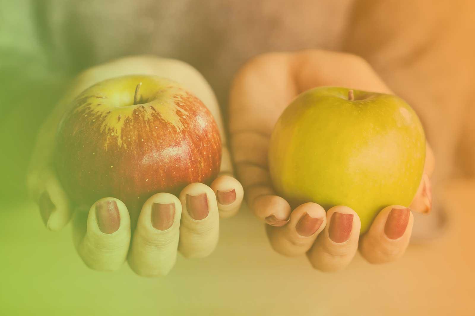 Imagem de uma mulher segurando uma maça verde na mão esquerda e uma maça vermelha na mão direita.