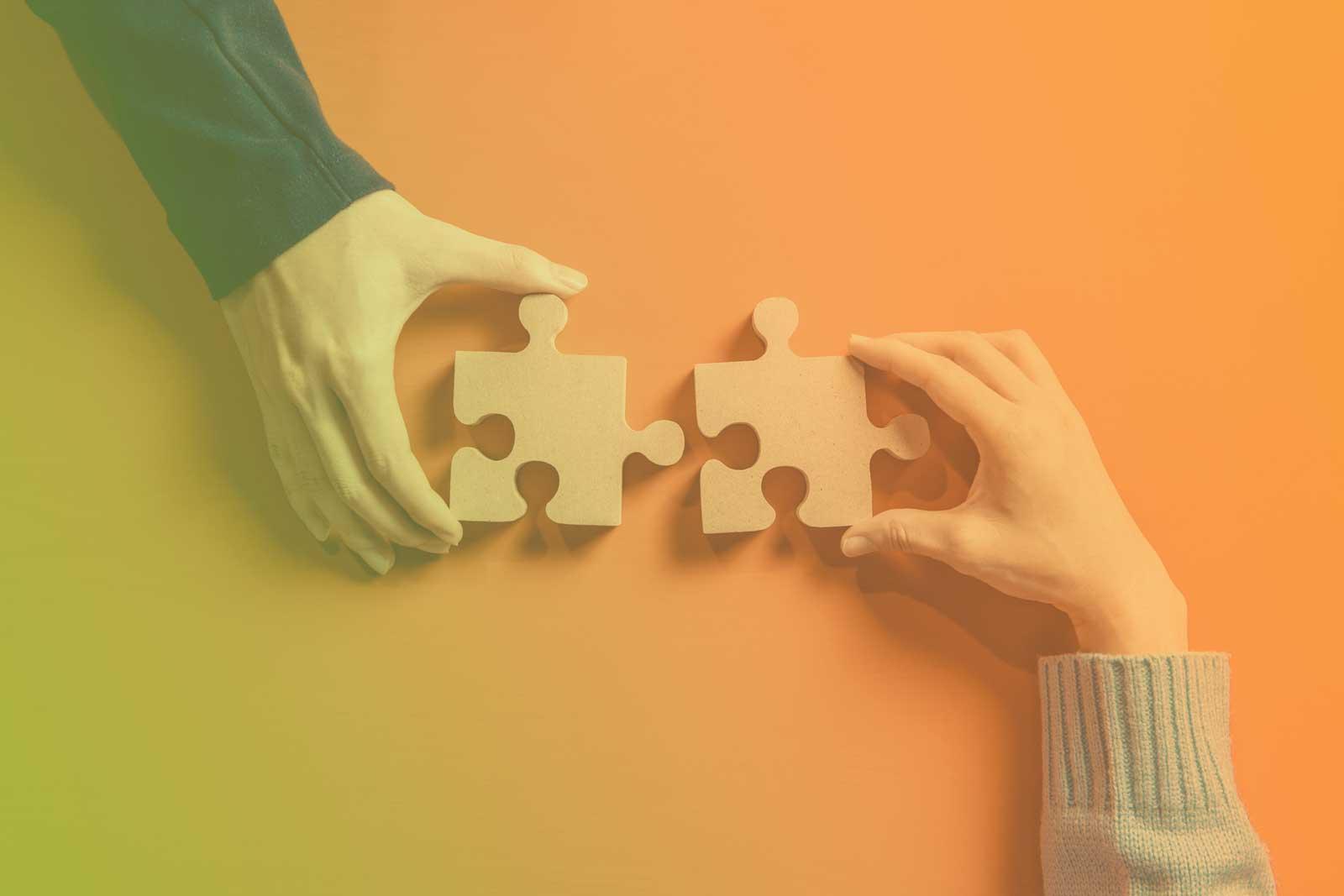 Foto de 2 pessoas segurando peças de um quebra-cabeça