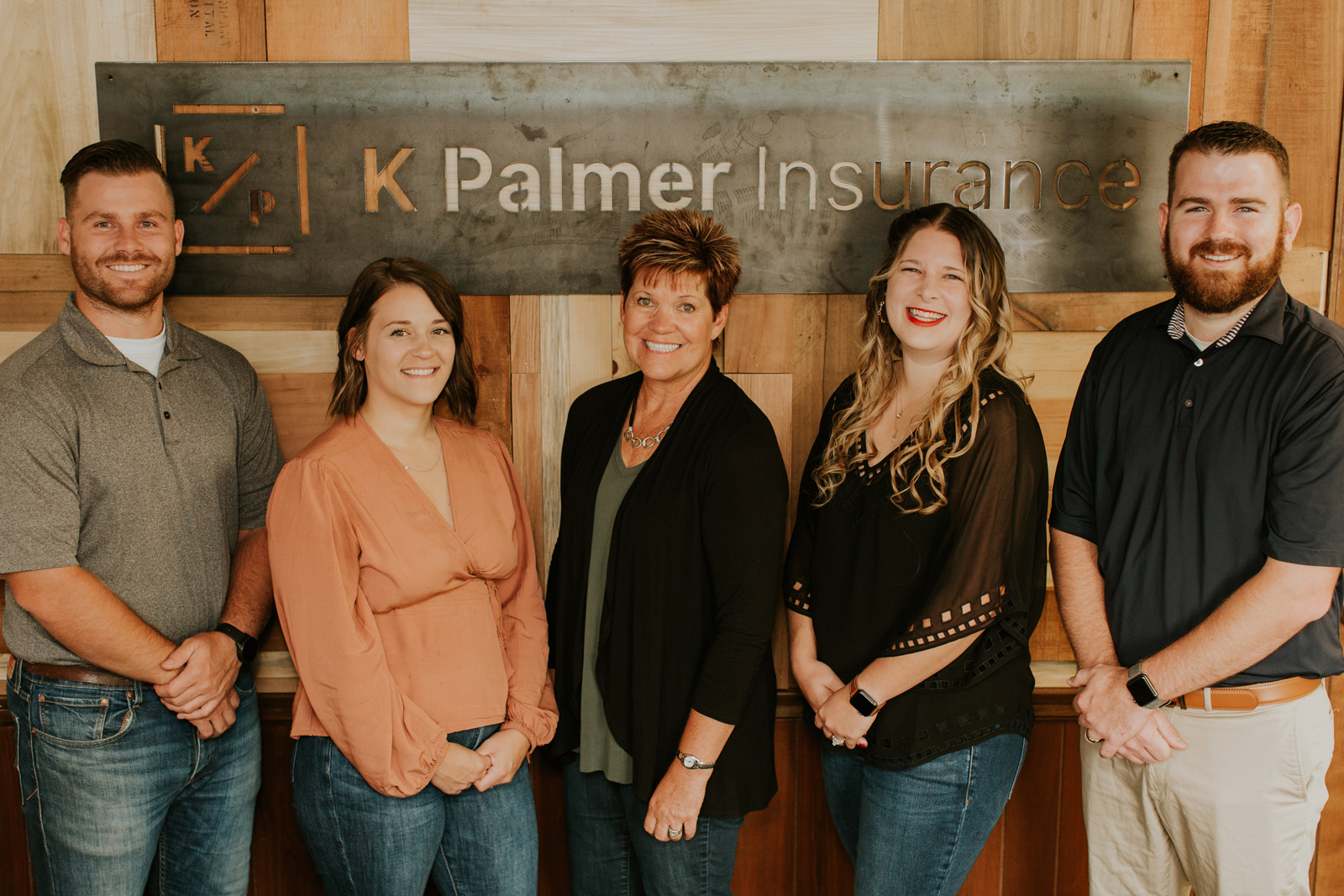 A happy K Palmer team standing in front of a wall with a logo.