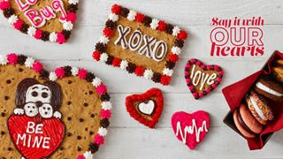 Great American cookies decorate for valentines day with hearts and pink and red frosting