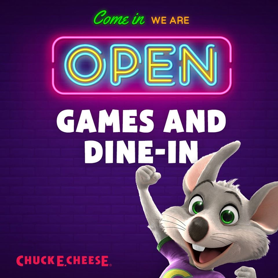 grey Chuck E Cheese mouse mascot with pink and blue neon open sign