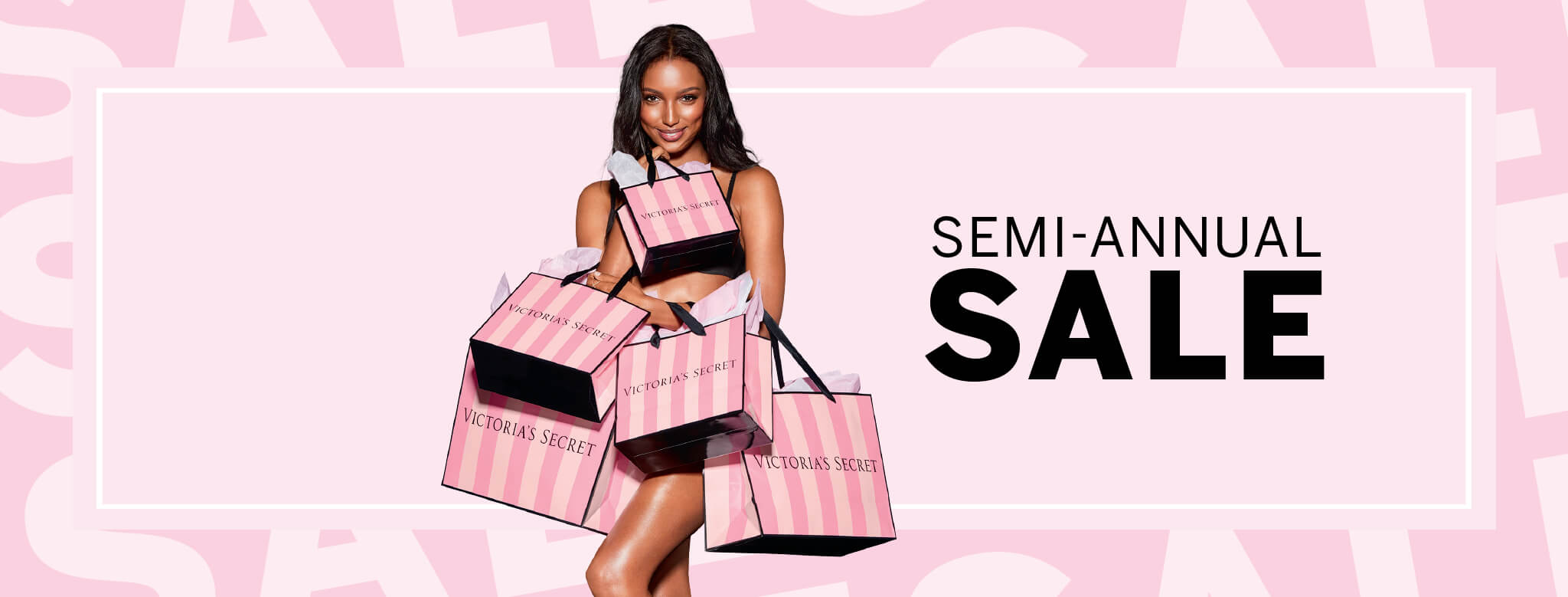 "Photo of a woman holding several Victoria's Secret Bags with the text ""Semi Annual Sale"" alongside her."