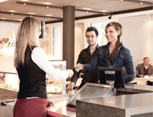 Raschen Zahlvorgang mit Karte hingehalten in Bäckerei Burkhard