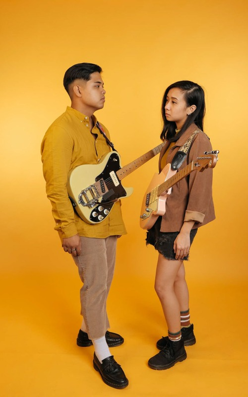 Indie rock pop duo Ragamuffs posing during a photo shoot with a yellow backdrop.