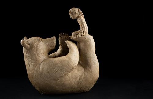 Sculpture réalisée par Sophie Verger en bronze, d'une fille nommée Gaby qui joue sur le ventre de son ours