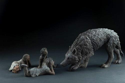 Sculpture réalisée par Sophie Verger en bronze qui représente 3 enfants regroupés devant un loup qui à l'air peureux.