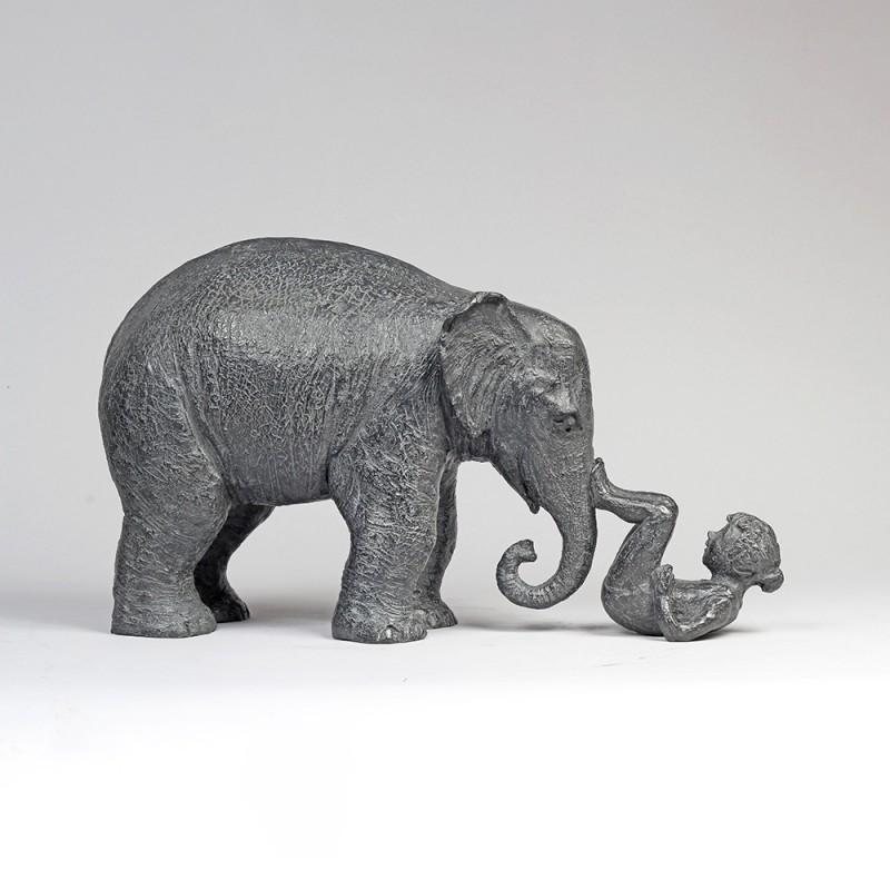 Sculpture réalisée par Sophie Verger en bronze, d'un éléphant qui joue avec une petite fille couchée sur le dos.