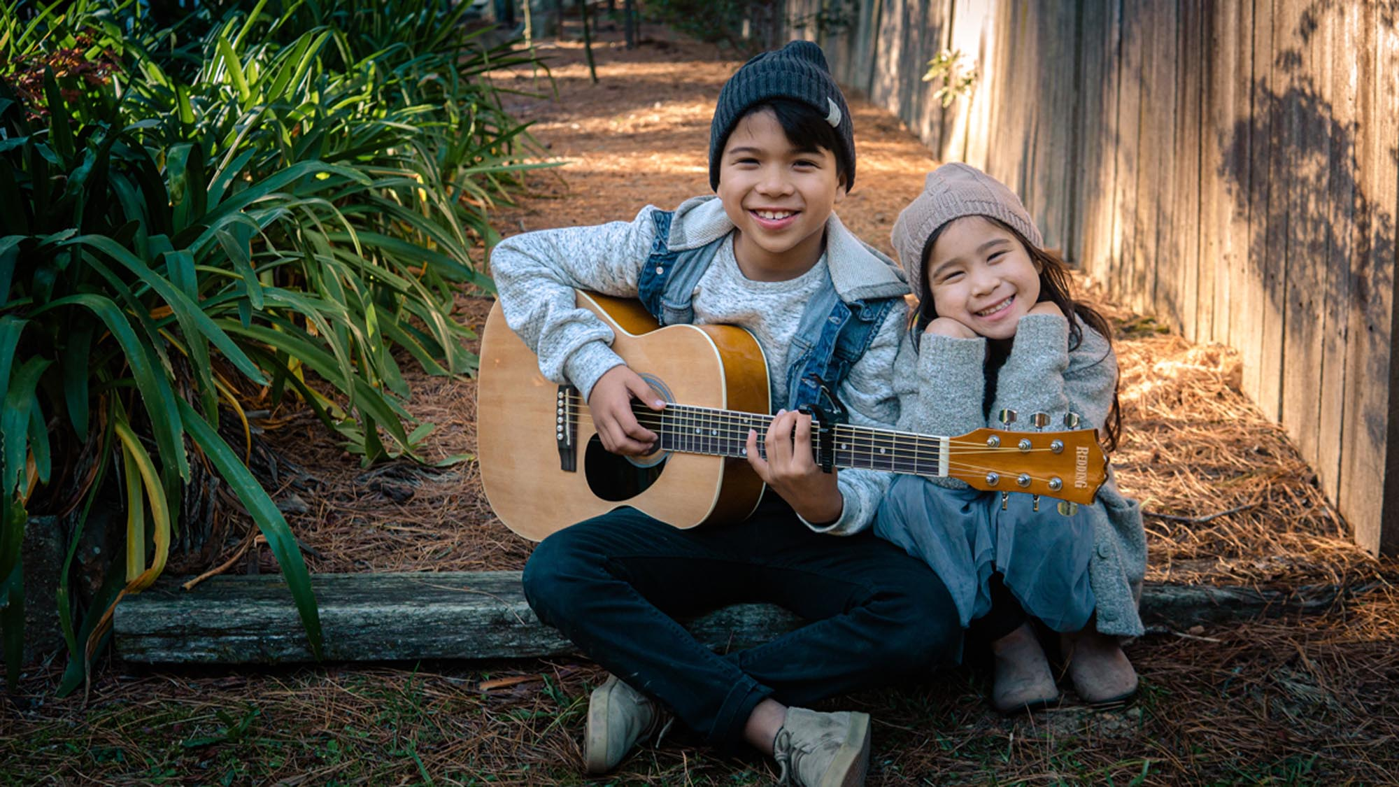 smiling children playing the guitar