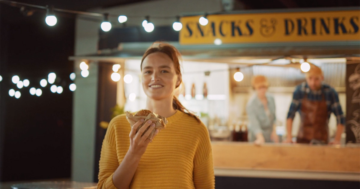 photo of a girl eating a burger