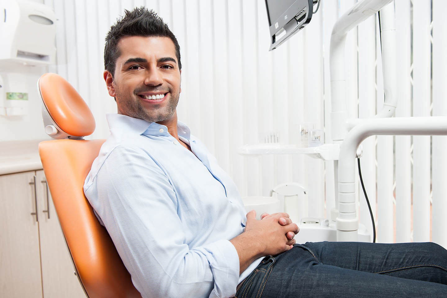 man leaning back in dentist chair smiling