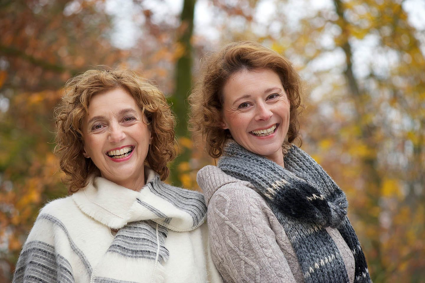 two woman smiling outside