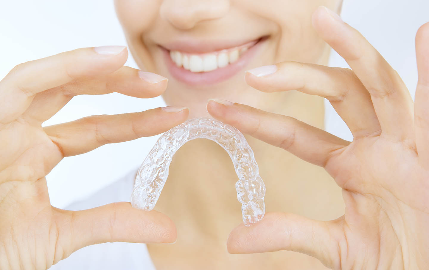 person smiling holding clear aligner