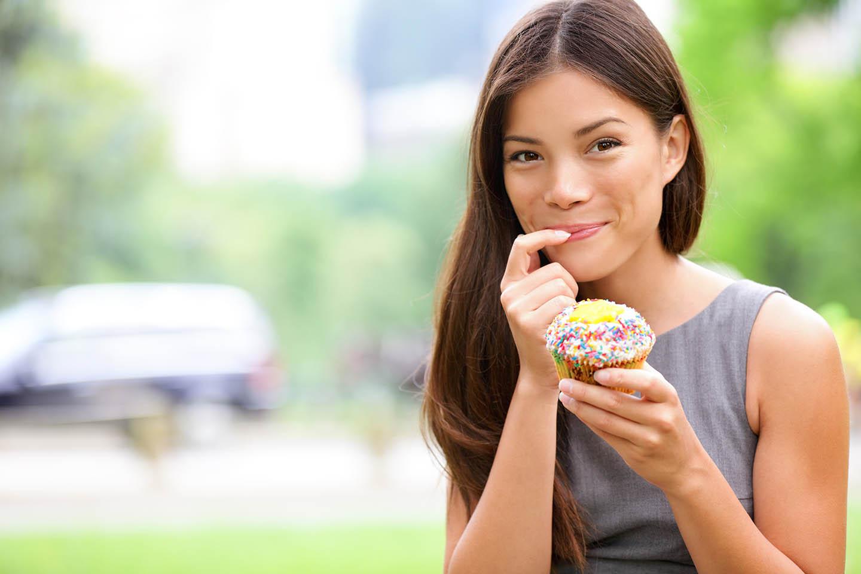woman smiling holding cupcake