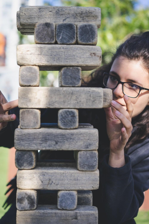 Woman scoping her next move in giant Jenga blocks game