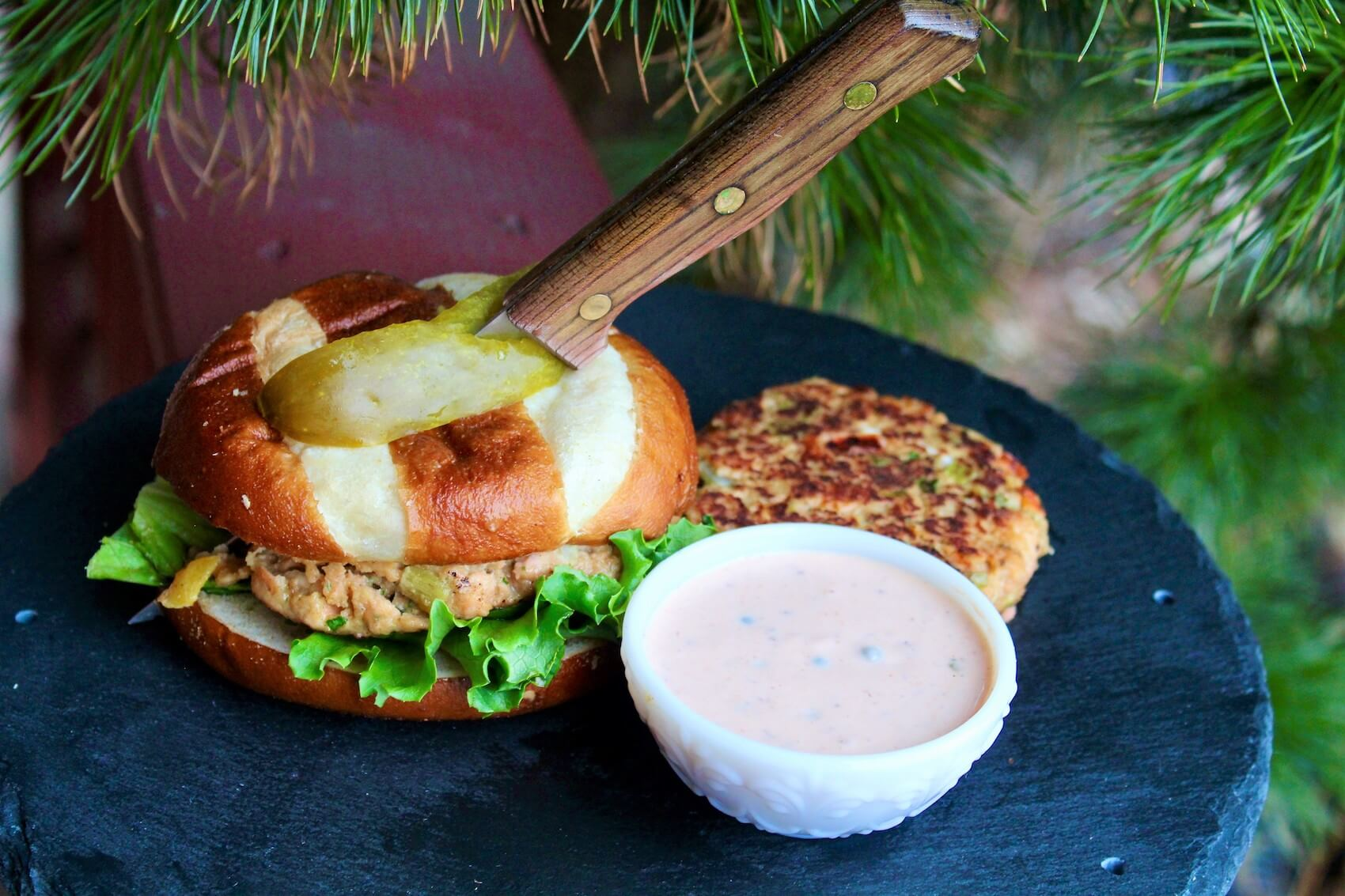 Salmon burger with a pickle slice on top and sauce on the side