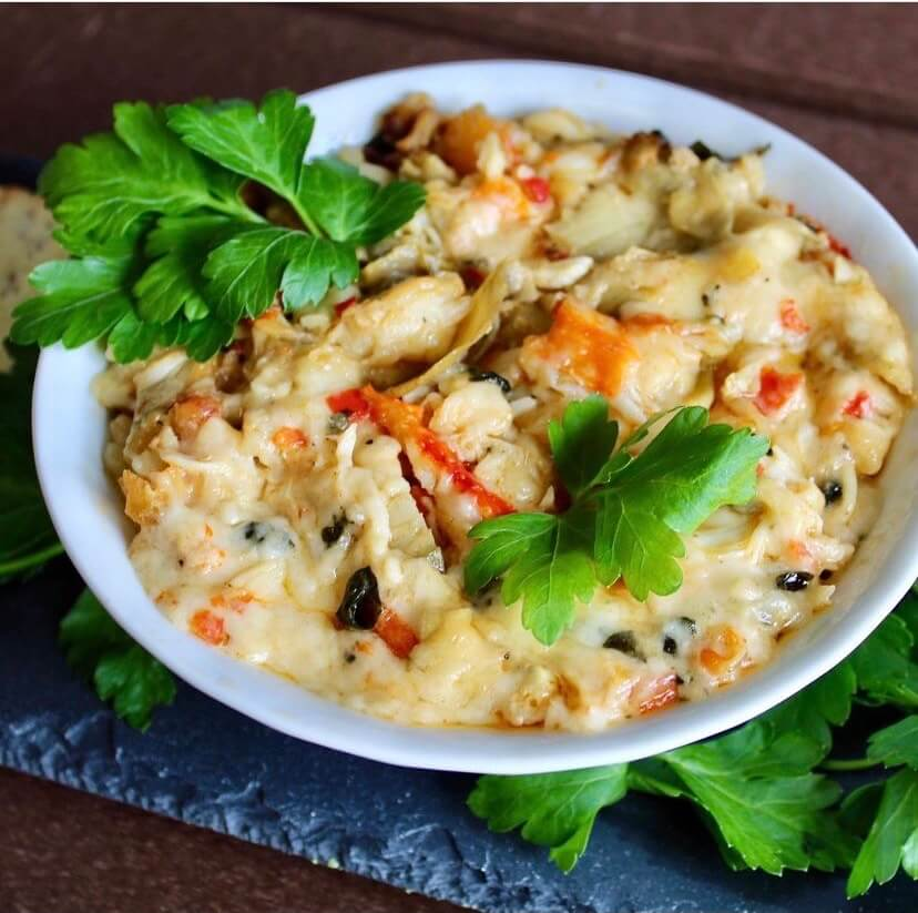 King crab dip in a bowl with Parsley garnish