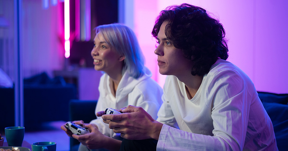 Man and woman playing a game on a console