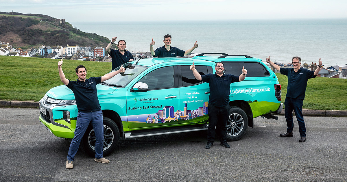 Lightning Fibre Team standing in front of their car in Hastings