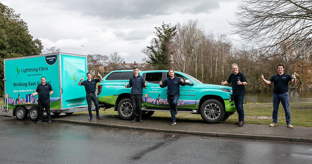 Lightning Fibre staff standing in front of a Lightning Fibre car and trailer