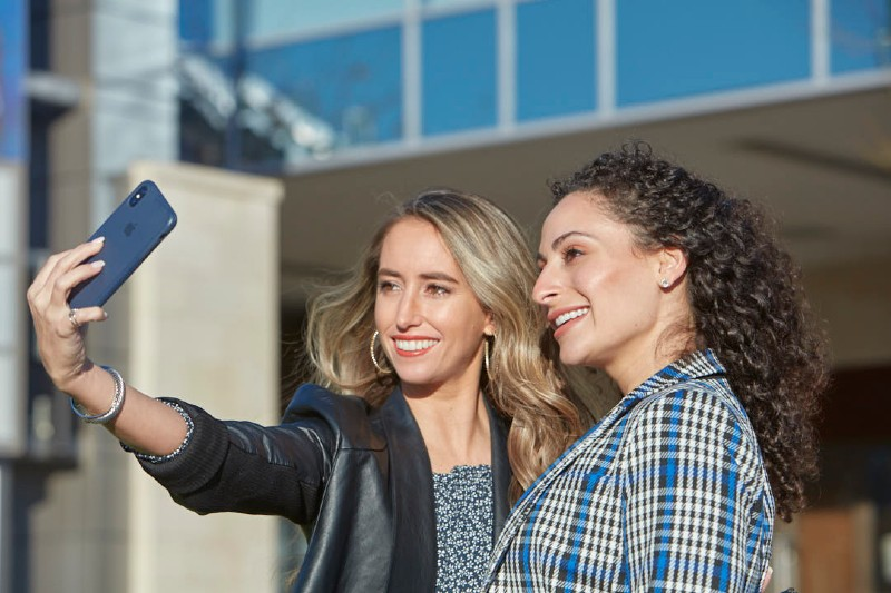 two woman taking a selfie and smiling
