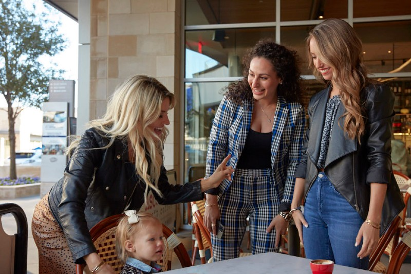 A group of women talking and smiling outside a resturant