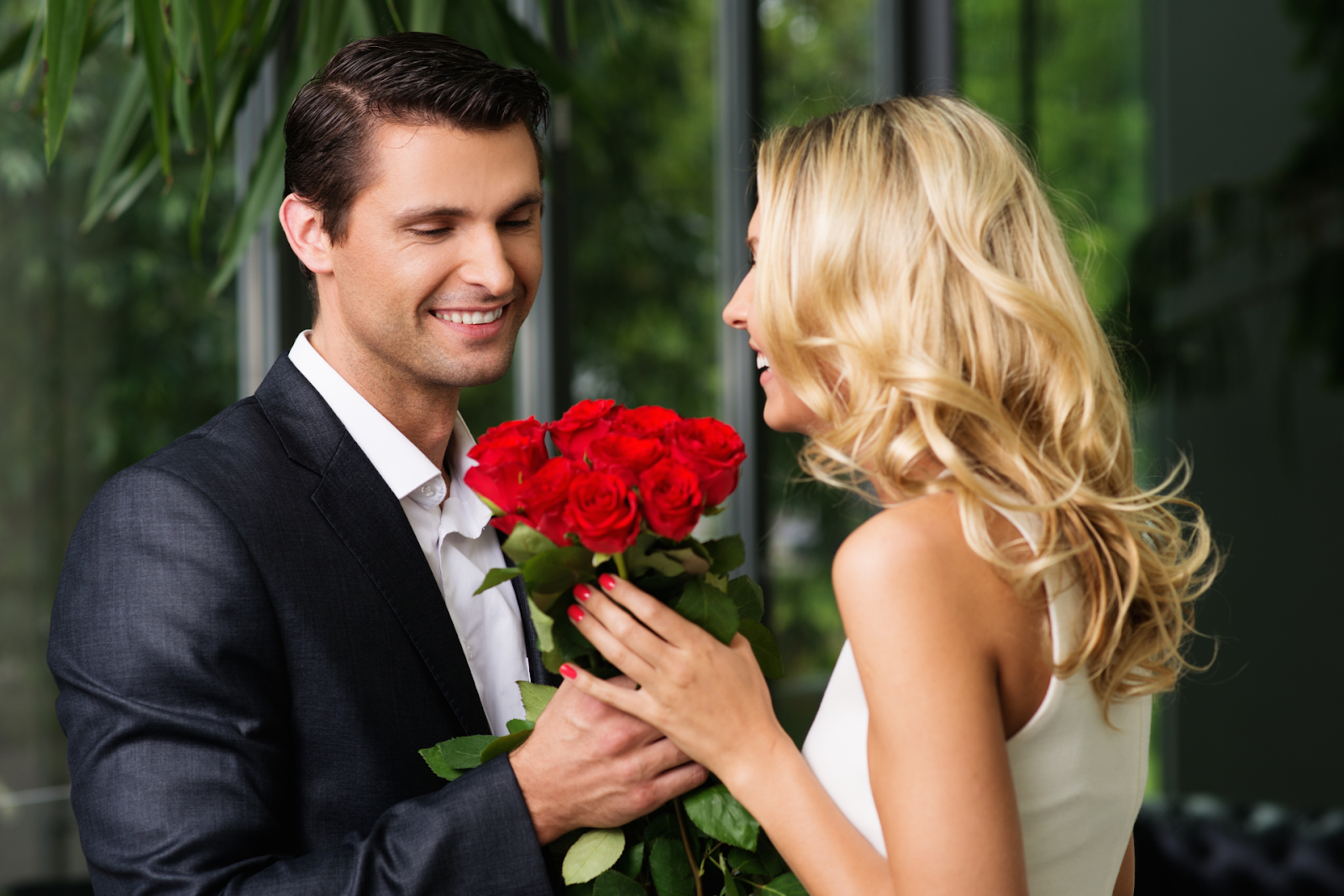 man giving woman bouquet of red roses