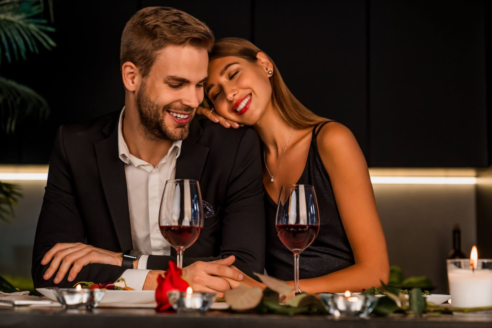 Woman resting head on man's shoulder at dinner