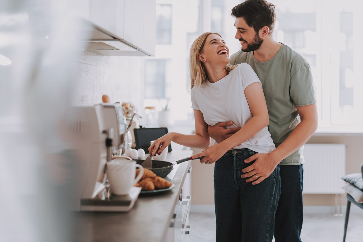 Man hugging woman from behind in a kitchen