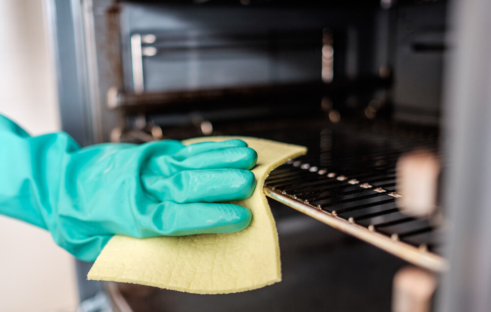 Man's hand with green gloves cleaning the kitchen oven