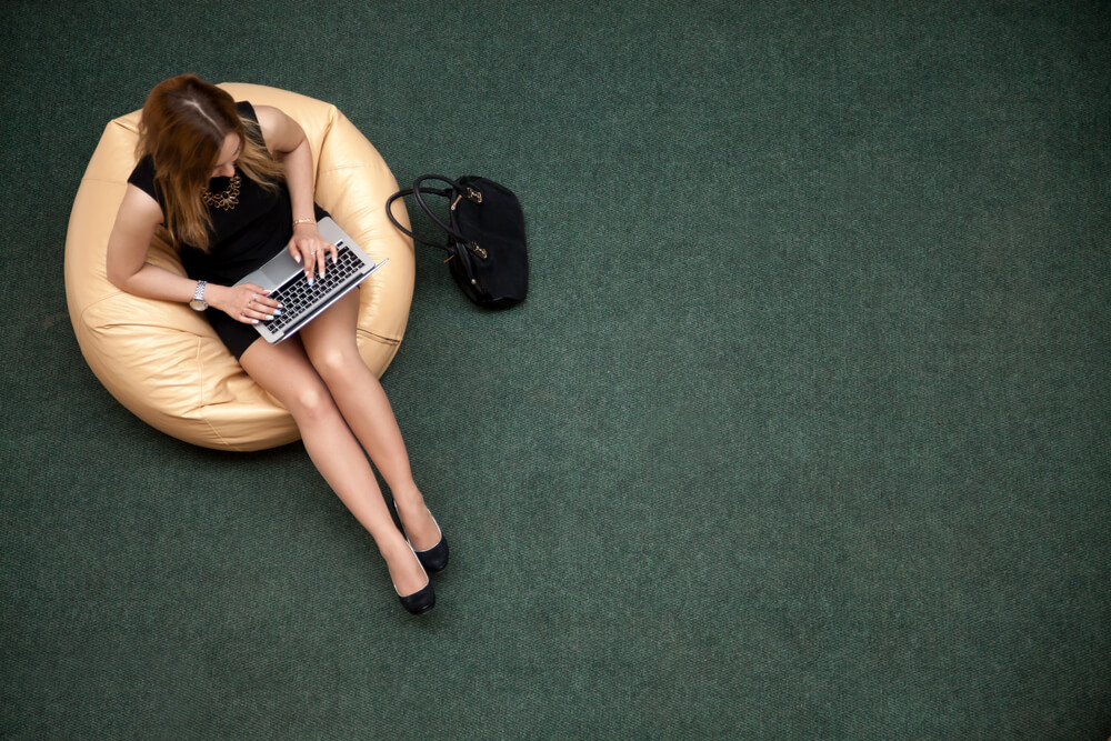 Young woman sitting in the office with green carpet on the background floor