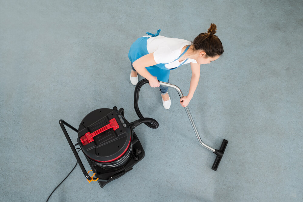 Young Female cleaning staff cleaning the office carpet with Vacuum Cleaner