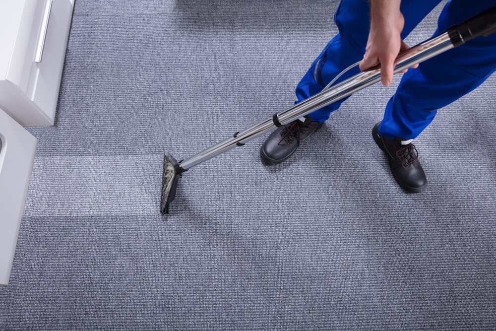 man cleaning gray carpet
