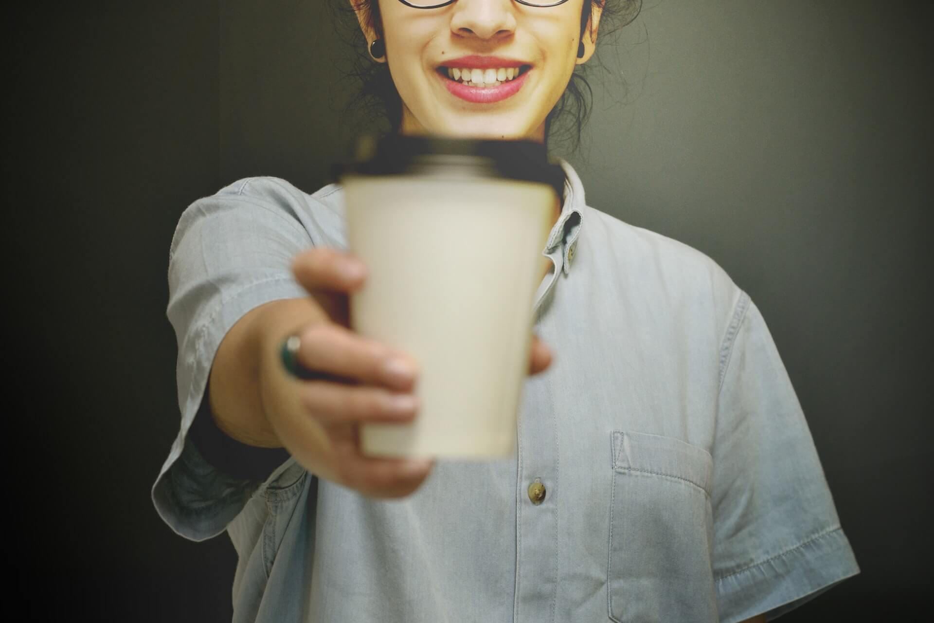 business woman holding a closed cup coffee in the office
