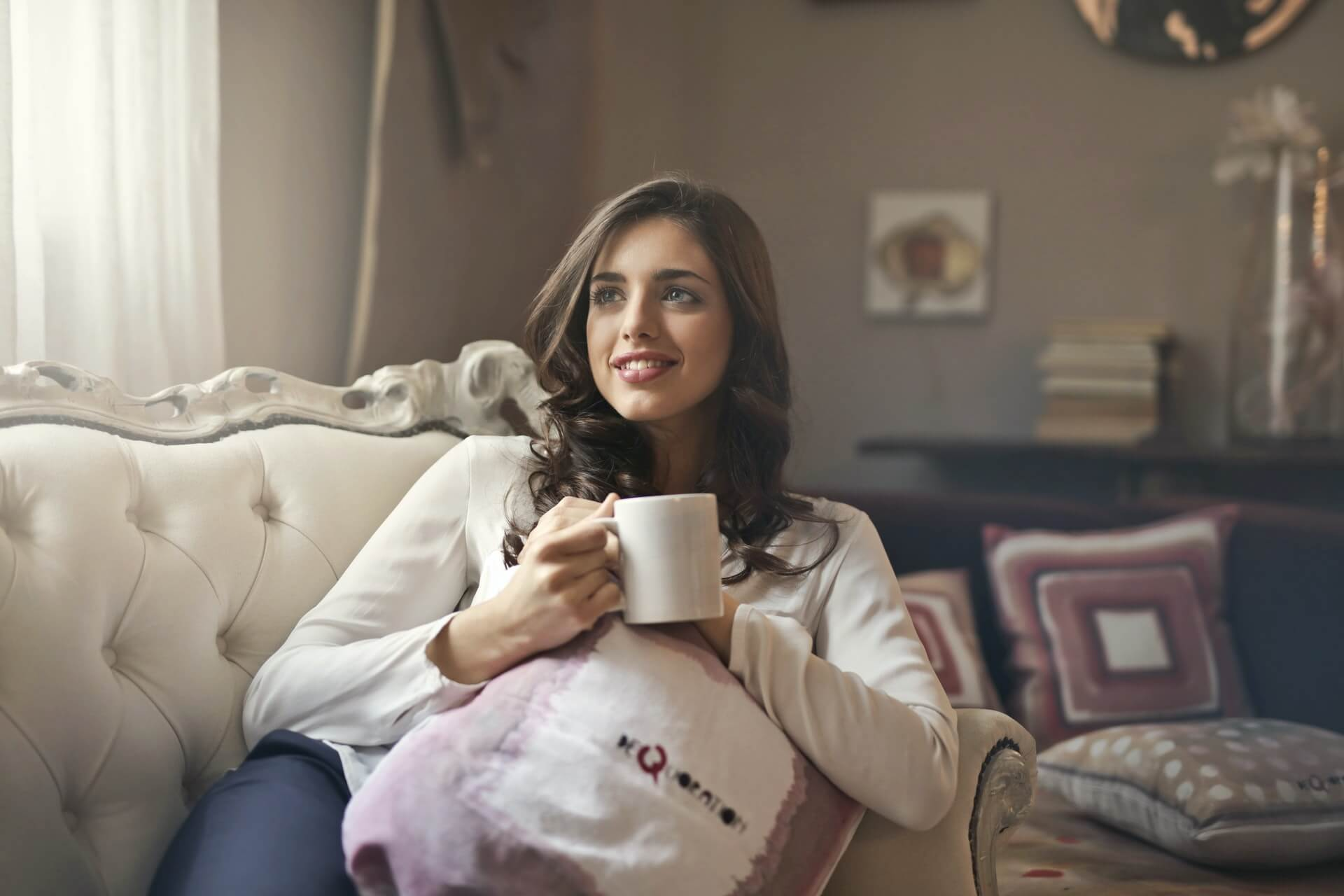 girl with a up of coffee sitting in her living room
