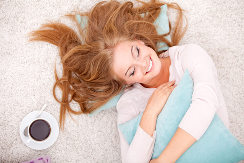 happy woman lying on the a freshly cleaned carpet after professional carpet cleaning service