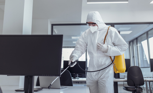 man in white protection suite disinfecting a commercial office space