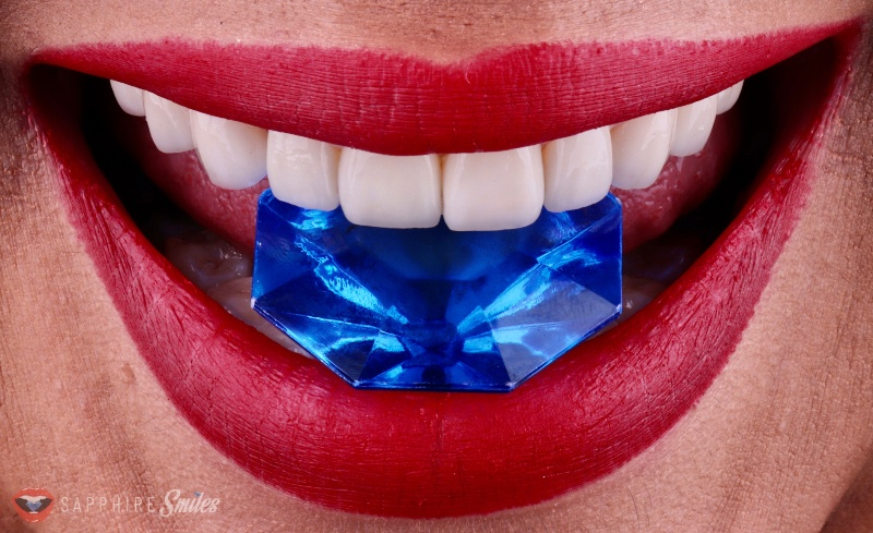 close up of mouth with beautiful teeth biting a sapphire