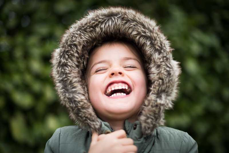 little boy laughing in winter coat