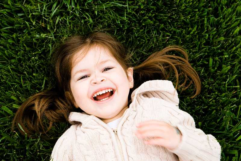 little girl laying in grass smiling