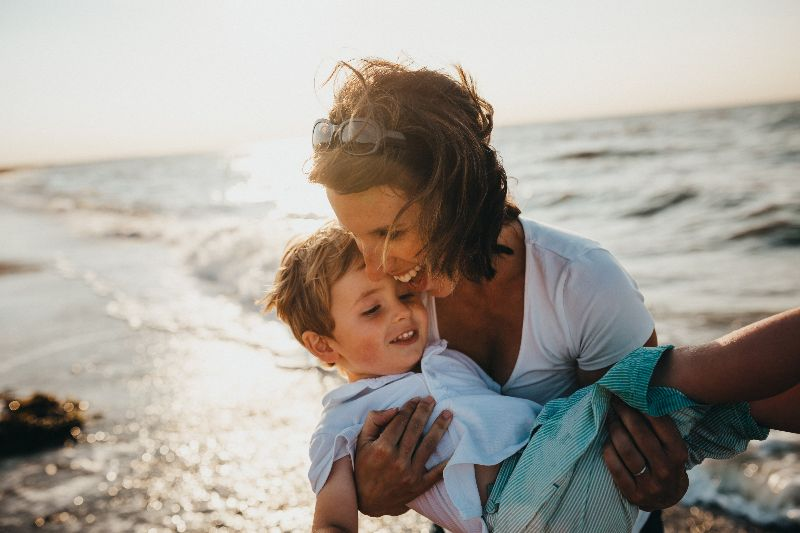 woman holding son at the beach