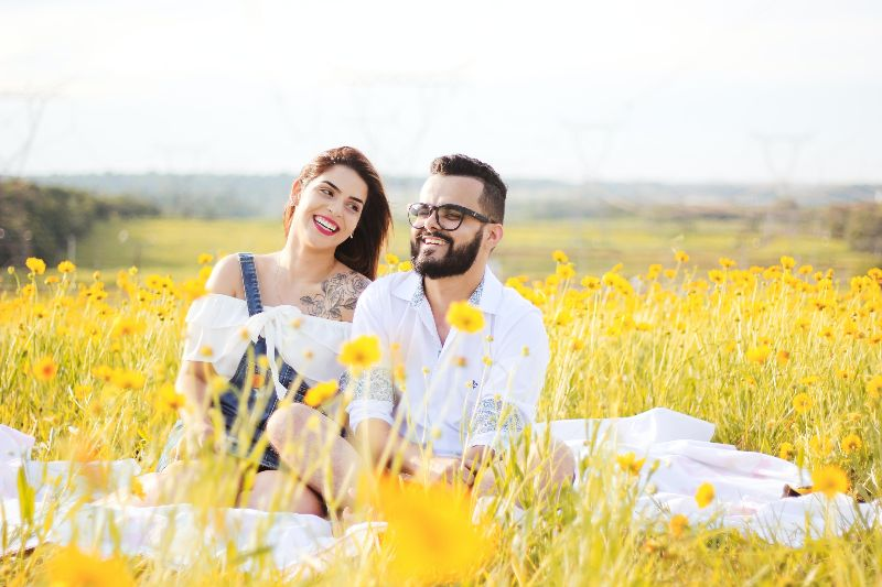 couple smiling in the field of flowers