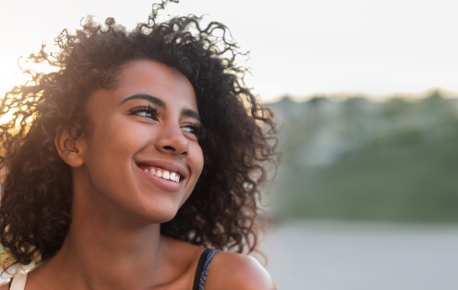 woman smiling in front of fence