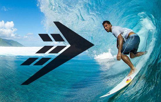 Mann auf Surfboard surft eine große Welle, links davon das Firewire Logo in schwarz