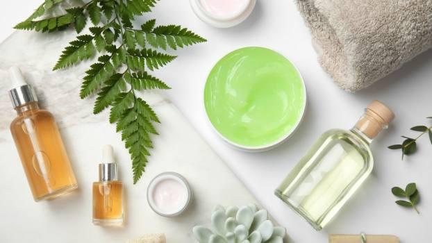 Global Beauty Care Stillleben-Bild mit Kosmetika, Pflanze und Handtuch