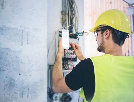 Bauarbeiter prüft Stromkasten, Branche: Dienstleistung