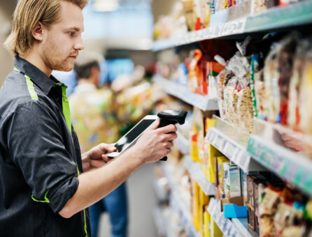 Verkäufer steht vor Supermarkt-Regal, Branche: Einzelhandel