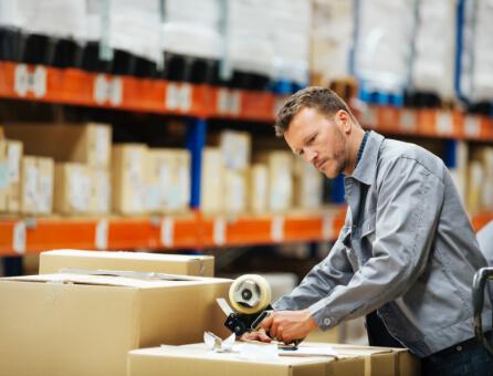 Mann beim Zukleben von Paket in Lagerhalle mit gefüllten Lagerregalen im Hintergrund, Branche: Großhandel