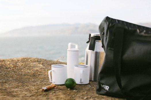 weiße Mirr Trinkbecher und Thermosflaschen mit schwarzer Tasche auf Erdboden, Outdoor-Szene