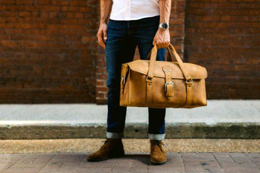 Mann auf Straße mit Traveler Bag in beige aus Leder
