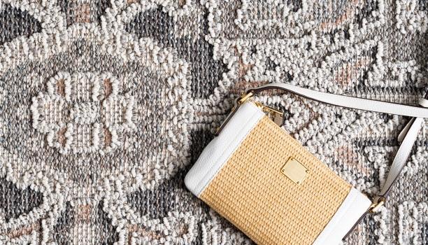 weiße Handtasche mit Korb-Muster und Struktur auf Teppich